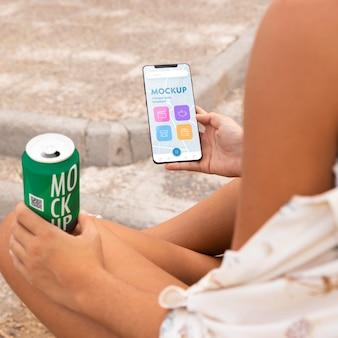 Kobieta sprawdza swój smartfon podczas picia sody