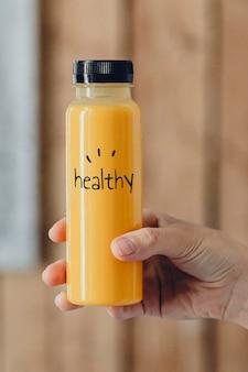 Kobieta trzyma butelkę soku pomarańczowego makieta