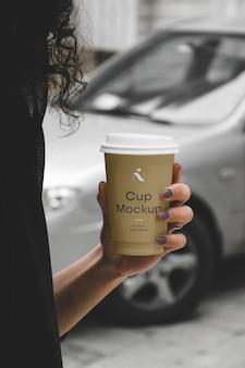 Kobieta trzyma makieta filiżanki kawiarni
