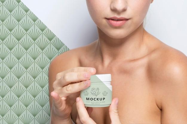 Kobieta trzyma makietę produktu do pielęgnacji skóry
