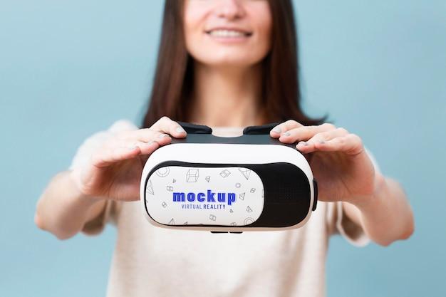 Kobieta trzyma słuchawki wirtualnej rzeczywistości