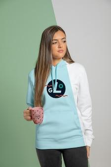 Kobieta ubrana w bluzę z kapturem, trzymając kubek