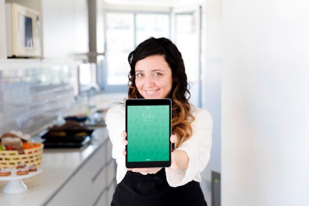 Kobieta w kuchni przedstawia tablet makieta