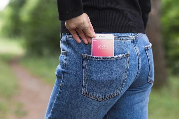 Kobieta w naturze z smartphone w kieszeni