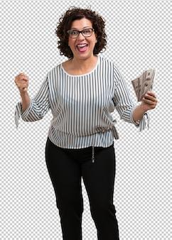 Kobieta w średnim wieku bardzo podekscytowana i euforyczna, krzycząca z niecierpliwością, świętująca zwycięstwo i sukces wygranej na loterii, trzymająca w ręku banknoty, koncepcja szczęścia