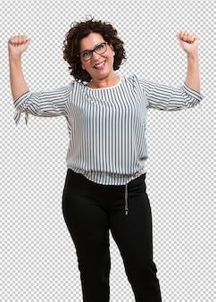 Kobieta w średnim wieku bardzo szczęśliwa i podekscytowana, podnosząca ręce, świętująca zwycięstwo lub sukces, wygrywająca na loterii
