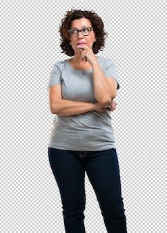 Kobieta w średnim wieku ma wątpliwości i jest zdezorientowana, zastanawia się nad pomysłem lub martwi o coś