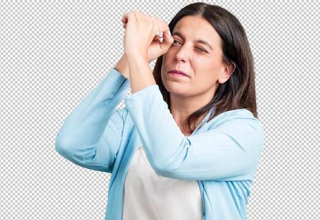 Kobieta w średnim wieku, patrząc przez szczelinę, chowając się i mrużąc oczy