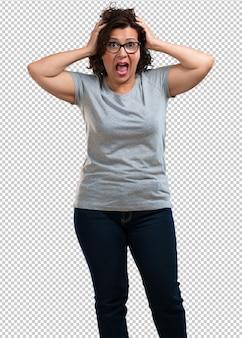 Kobieta w średnim wieku sfrustrowana i zrozpaczona, zła i smutna z rękami na głowie