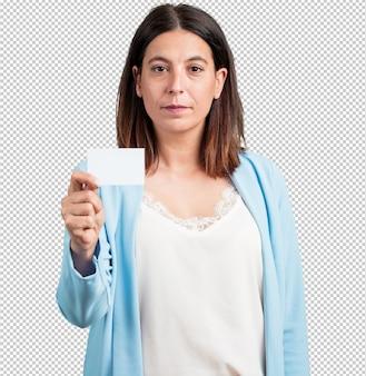 Kobieta w średnim wieku, uśmiechnięta, pewna siebie, oferująca wizytówkę, ma dobrze prosperującą firmę, kopiuje przestrzeń, aby pisać cokolwiek chcesz