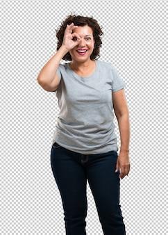 Kobieta w średnim wieku wesoła i pewna siebie, robi ok gest, podekscytowana i krzycząca, aprobaty i sukcesu