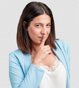 Kobieta w średnim wieku zachowuje tajemnicę lub prosi o ciszę, poważną twarz, pojęcie posłuszeństwa