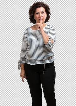 Kobieta w średnim wieku zachowuje tajemnicę lub prosi o ciszę, poważną twarz, posłuszeństwo