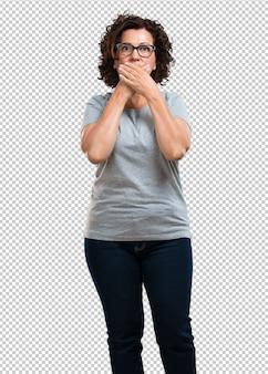 Kobieta w średnim wieku zakrywająca usta, symbol ciszy i represji, starająca się nic nie mówić