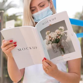 Kobieta z maską na ulicy czytania książki