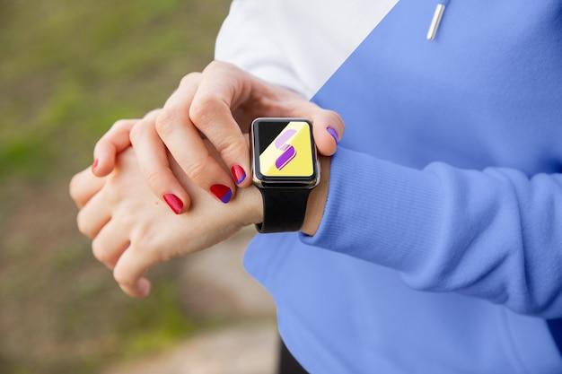 Kobieta z zegarek z kapturem sprawdzania