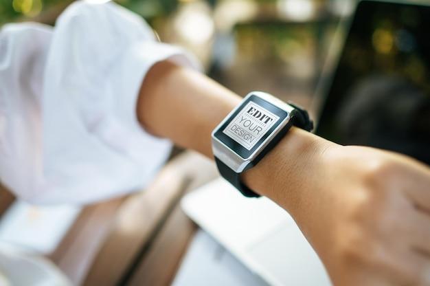 Kobieta za pomocą makiety inteligentnego zegarka