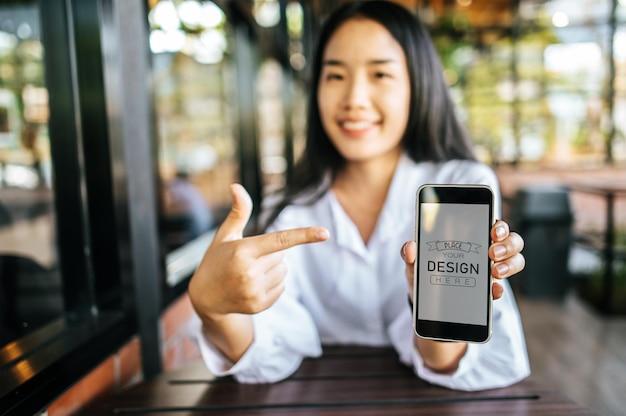 Kobieta za pomocą makiety smartphone psd