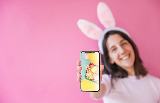 Kobiety mienia smartphone mockup dla easter