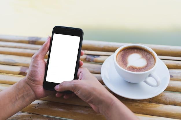 Kobiety ręka trzyma smartphone makietę na bambusowym stole, gorąca kawa espresso, plenerowa