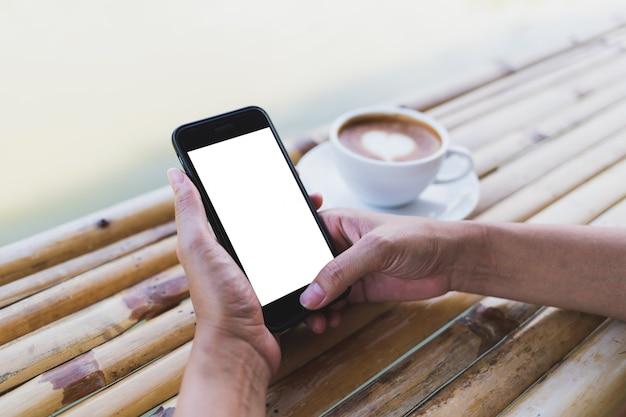 Kobiety trzyma smartphone makietę na bambusowym stole