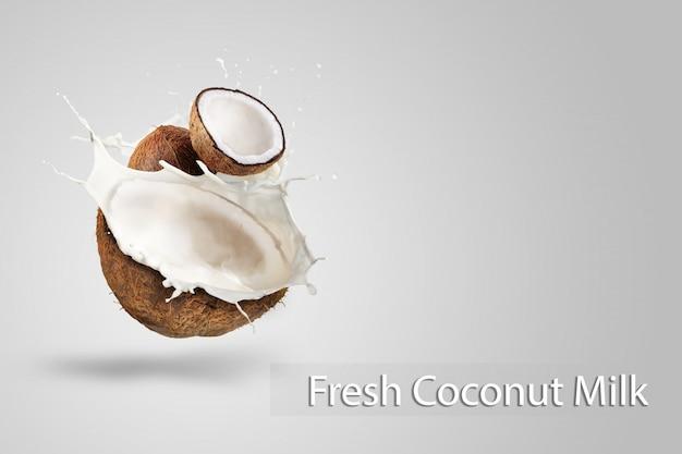 Kokosowego mleka chełbotanie odizolowywający na zielonym tle