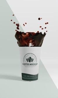 Kompozycja papierowego kubka do kawy z odrobiną kawy