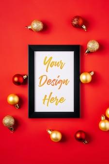Kompozycja świąteczna z makietą ramki na zdjęcia. czerwone i złote ozdoby i bombki.
