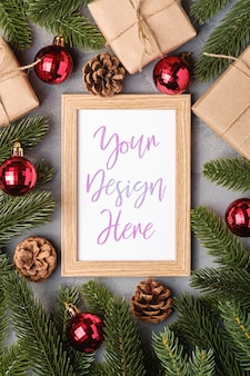 Kompozycja świąteczna z makietą ramki na zdjęcia, czerwonymi bombkami, prezentami i gałęziami jodły