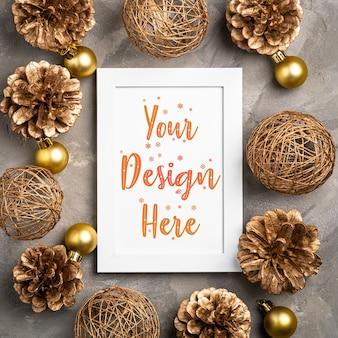 Kompozycja świąteczna z pustą ramką na zdjęcia. złoty ornament, ozdoby z szyszek. makiety szablonu karty pozdrowienia