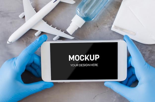 Koncepcja planowania podróży, koronawirus i kwarantanna. ręce w jednorazowych rękawiczkach trzymają smartfon. makiety z miejsca kopiowania. model samolotu, maska na twarz i spray dezynfekujący do rąk.