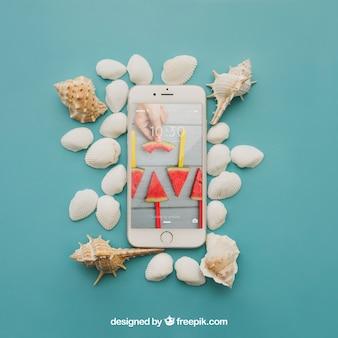 Koncepcja plaży z smartphone i muszli