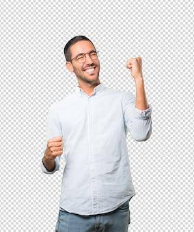 Konkurencyjny młody człowiek robi gestowi świętowanie