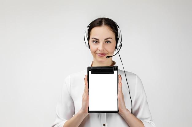 Konsultant call center w słuchawkach trzyma schowek