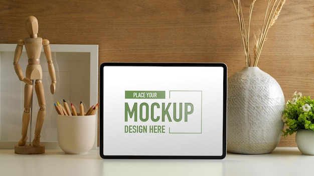 Kreatywne miejsce do pracy z makietą cyfrowego tabletu, ołówkami i dekoracjami w domowym biurze