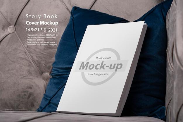 Książka z makietą pustej okładki na aksamitnej niebieskiej poduszce sofy