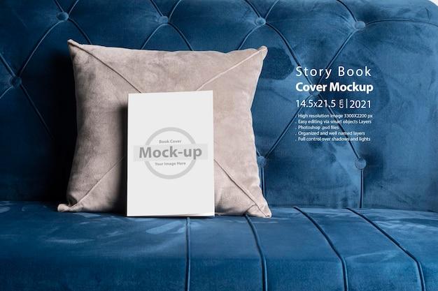 Książka z pustą okładką na niebieskiej sofie z aksamitnej poduszki