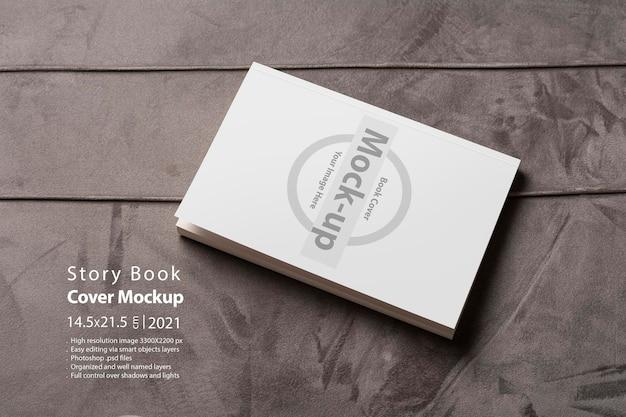 Książka z pustą okładką na szarej aksamitnej powierzchni sofy, edytowalna seria makiet z inteligentnymi warstwami obiektów gotowych do projektowania
