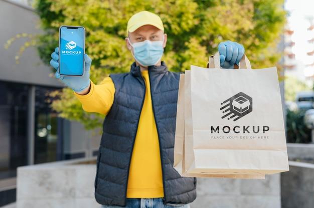 Kurier trzymający makieta telefonu i torby
