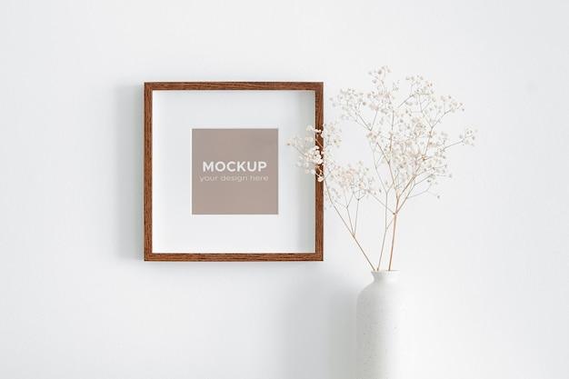 Kwadratowa ramka na zdjęcia na białej ścianie z dekoracjami suchych roślin gipsowych