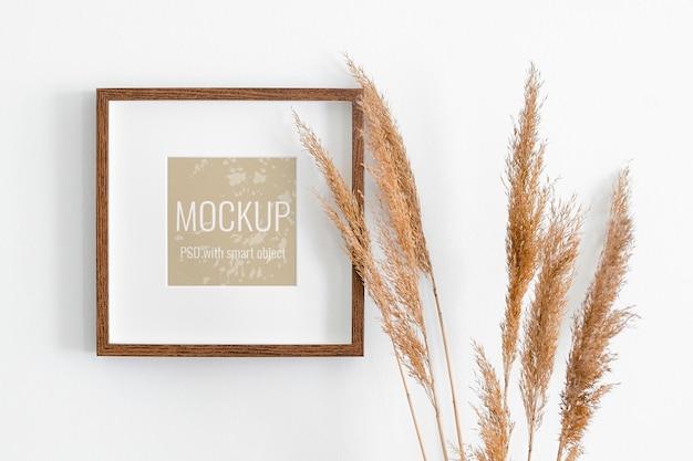 Kwadratowa ramka na zdjęcia na białej ścianie z dekoracjami suchych roślin