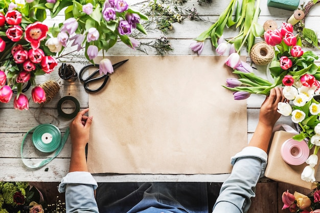 Kwiaciarnia pokazano pusty projekt papieru na drewnianym stole