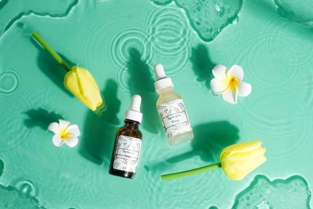 Kwiatowy zestaw z makietowymi butelkami naturalnego balsamu i kwiatami.