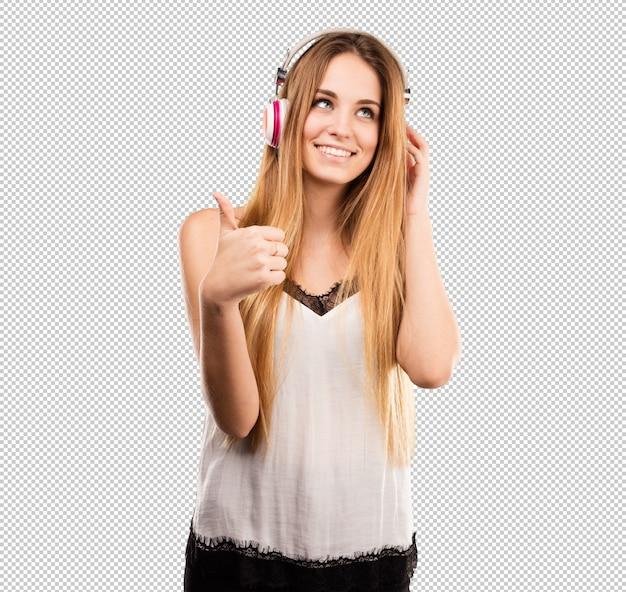 Ładna młoda kobieta słucha muzykę na hełmofonach