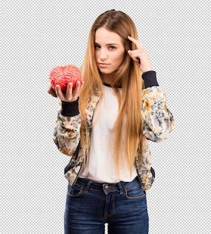 Ładna młoda kobieta trzyma móżdżkowego przedmiot