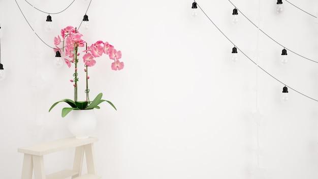 Lampy wiszące na białej ścianie i piękny dekoracyjny różowy kwiat