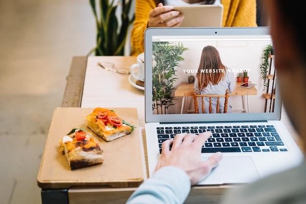 Laptop makieta z człowiekiem i panini