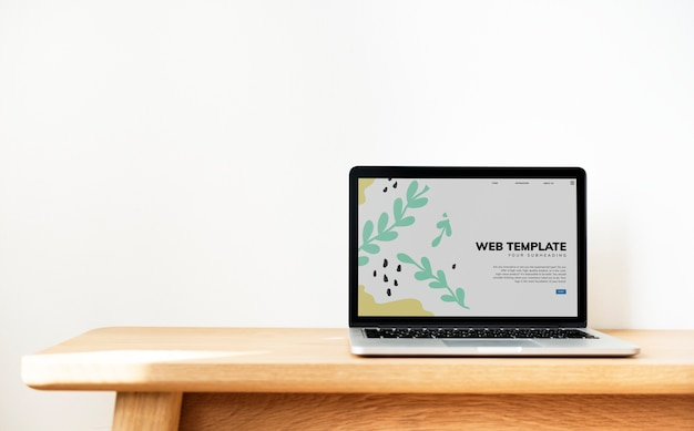 Laptop pokazuje strona internetowa szablon na drewnianym stole