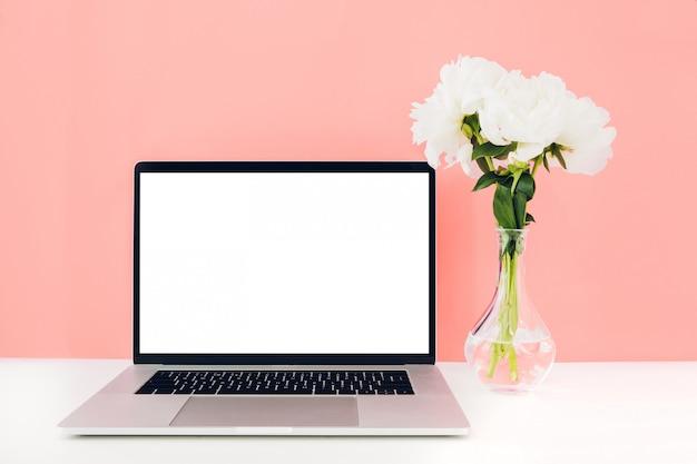 Laptop z białym pustym ekranem i kwiatami w wazonie na stole