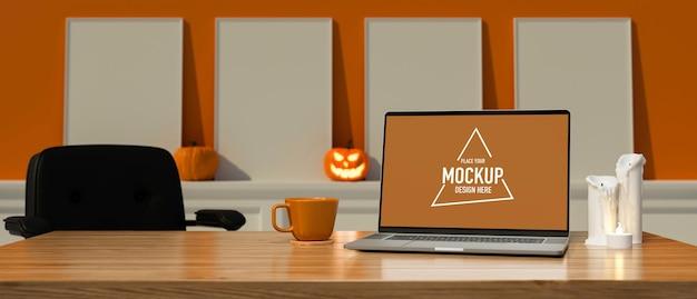 Laptop z makietą ekranu na stole w pokoju ozdobionym halloweenowymi dekoracjami